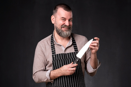 Portrait of a handsome male chef holding knife checking its edge.