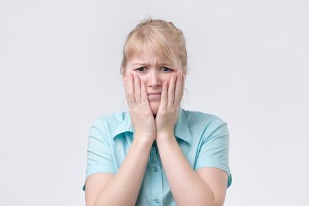 Cute blonde woman having looking tired holding her hand on cheek. Foto de archivo