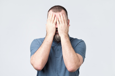 Man in blue t-shirt covering his face with hands Imagens