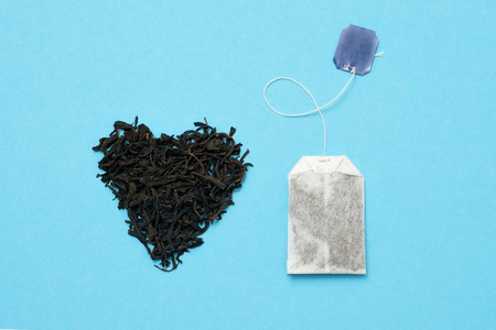 Tea bag and black leaves on blue background. What kind of tea is better
