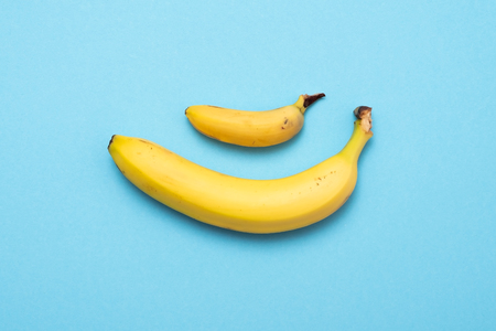 baby banana compare size with banana on blue background. size penis concept 写真素材