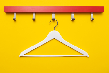 Wooden coat hanger or clothes hanger on a colored background. Final sale or black friday concept. 스톡 콘텐츠
