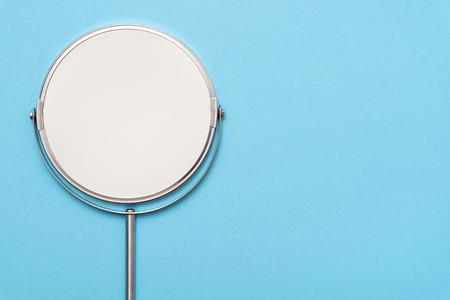 Top view image of circle hand mirror on blue background. Flat lay. Фото со стока