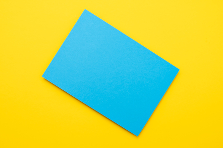 One blue paper on yellow background. Copyspace for your text. Imagens