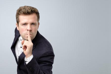 Handsome man in suit making silence gesture. Keep it in secret.