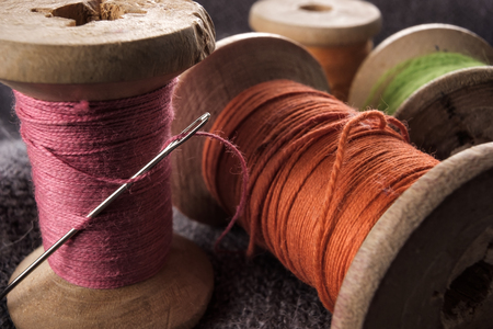 Sewing needle and cotton thread on wooden spool macro view. Hobby tailor detail Фото со стока