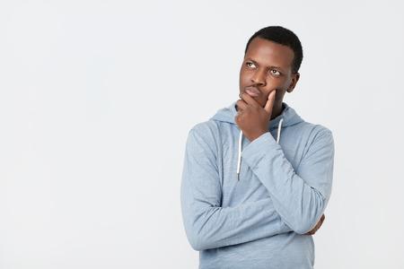 Apuesto joven afroamericano mirando hacia arriba con expresión pensativa y escéptica, tratando de recordar algo