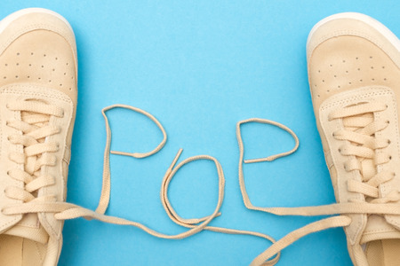 New women sneakers with laces in pop text. Flat lay on blue background.