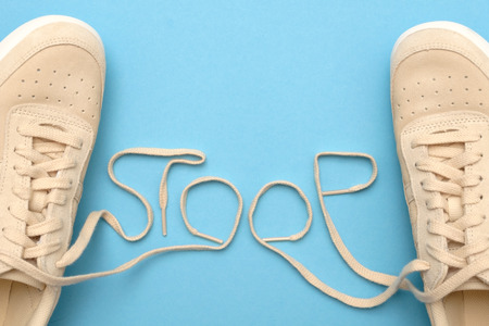 Women sneakers with laces in stoop text.