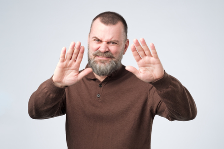 Mature man with beard shows refusal gesture, does not want to speak with you