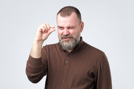 Mature caucasian man gesturing with hand showing small size Standard-Bild