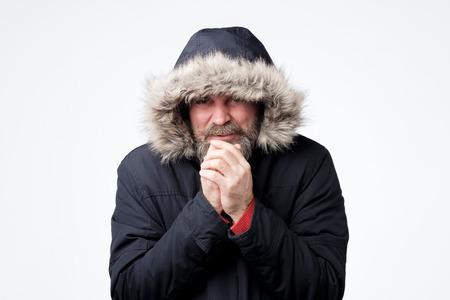 Mature man with beard with hood on head freezing