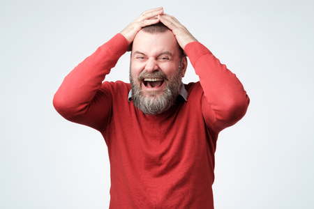Handsome mature bearded man in red sweater laughing