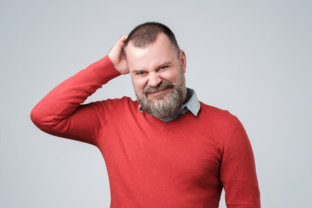 Confused man with beard scratching head looking at camera Stockfoto