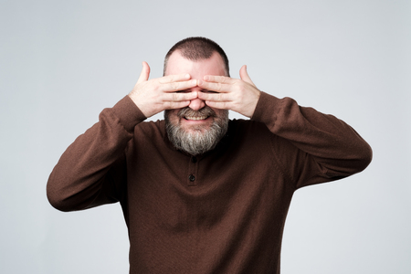 European mature man covering his face by hands Imagens