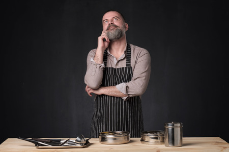 Bearded male chef showing different spices he uses. Secret of delicious food. Food, cooking, preparation concept. Professional food preparation concept.