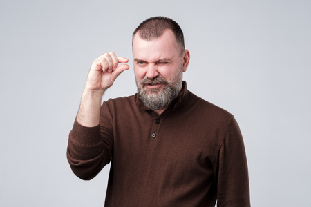 Mature man with beard in brown pulover shows something invisible being upset. Studio shot