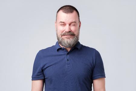 Homme mûr en chemise bleue froissée à cause du goût aigre. Grimaçant de la sensation ou du son désagréable