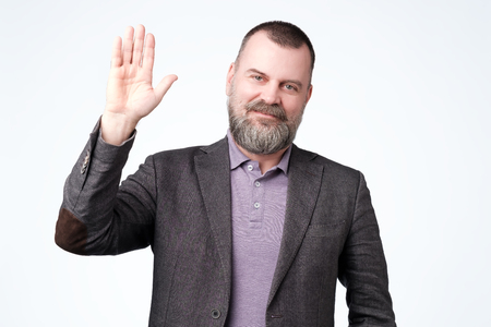 Mature man in jacket wave hand welcome. Studio shoot