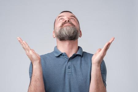 Mature man with beard in blue t-shirt asking from Heaven raising his hand. Studio shot
