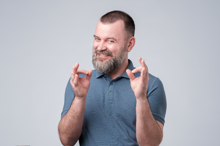 Mature guy in blue t-shirt showing ok or okay sign. Not bad, like your idea, good job. Positive human facial emotion. Studio shot