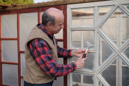 Senior bald man farmer cleans the window from the paint. Building a greenhouse on farm from old windows.