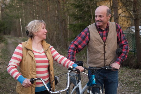 Happy elderly senior couple cycling in park together