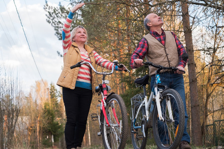 Heureux couple de personnes âgées à vélo dans le parc ensemble