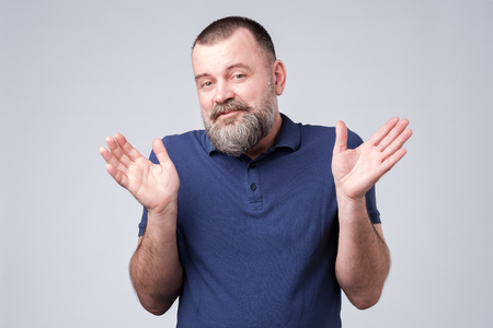 Unsure confused puzzled bearded man in blue t-shirt shrugging shoulders isolated over gray background
