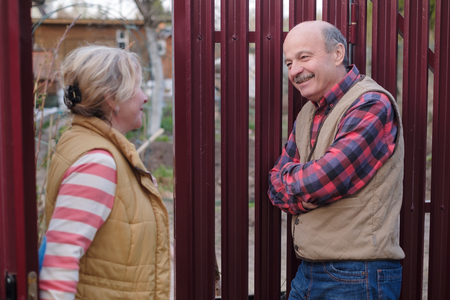 two senior neighbors takling to each other on sunny day near fence. They discuss important news