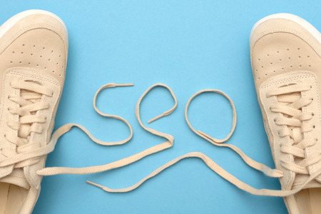 New women sneakers with laces in seo text. Flat lay on blue background.