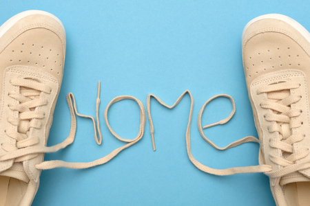 New women sneakers with laces in home text. Flat lay on blue background.