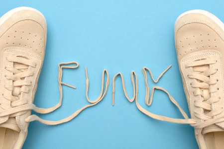 New women sneakers with laces in funk text. Flat lay on blue background.