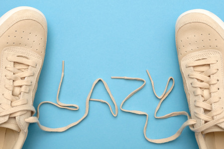 New women sneakers with laces in lazy text. Flat lay on blue background.