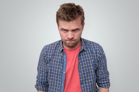 Angry young man looking at camera frowning