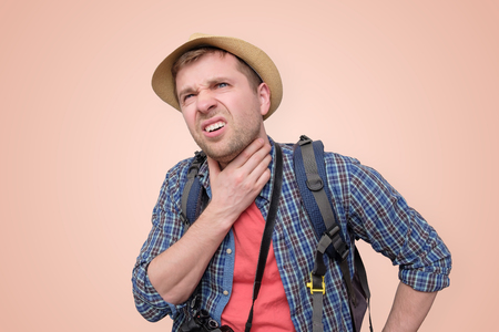 man in summer hat suffering from the pain in his throat