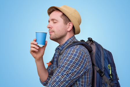 Young man wearing summer hat and holding cup