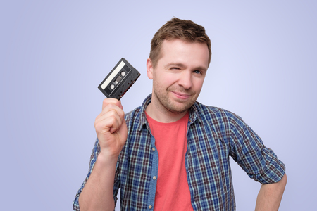 Young caucasian man with audio cassette tape smilinf on blue background 版權商用圖片