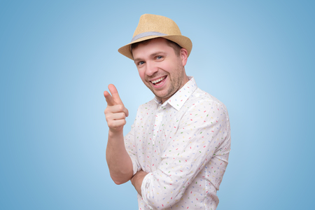 Cheerful man in summer hat pointing happily at you.