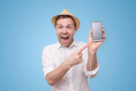 Funny young european man pointing to phone screen of his smartphone