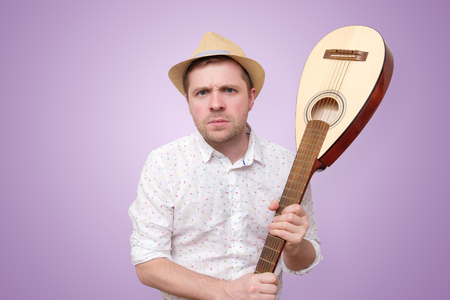 Angry man in summer hat hitting guitar