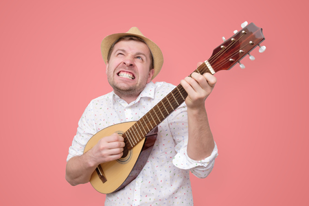 Man in summer hat playing guitar and singing songs.