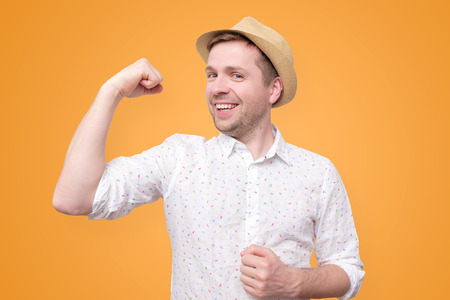 Young funny tourist man in summer hat shows biceps