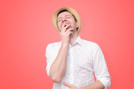 man in summer hat laughs loud on red wall 版權商用圖片