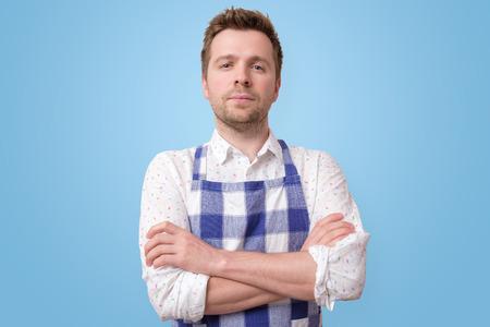 mature restaurant employee man on blue wall