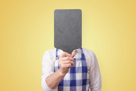 Man in apron holding cutting board near face