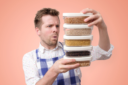 Young man in apron hold several boxes with grains