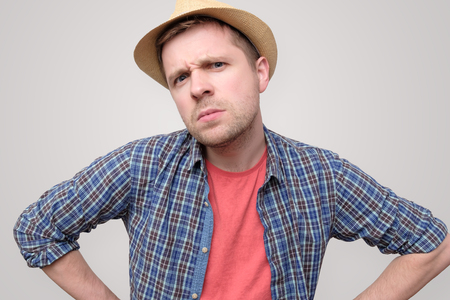 man in summer hat frowning being angry.