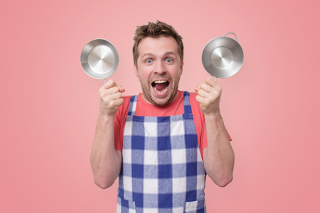 man in apron holding a metal pan in the studio
