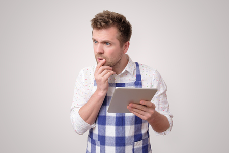 Man looking at recipe on digital tablet to prepare cake